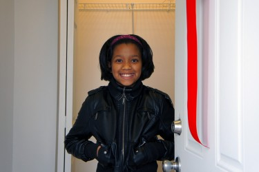A child greets you in front of her new home, purchased by her family with an affordable mortgage