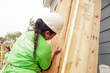 A Habitat Chicago volunteer sings a message on a home in progress
