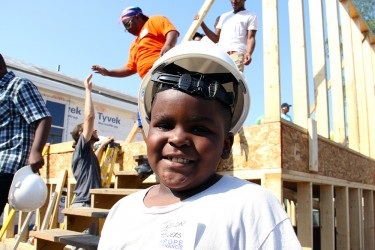 A child on the Habitat build site for his family's future home's wall raising
