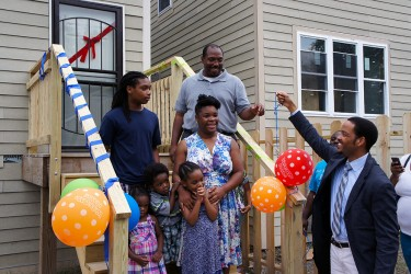 A family takes the keys to their new home, purchased with an affordable mortgage