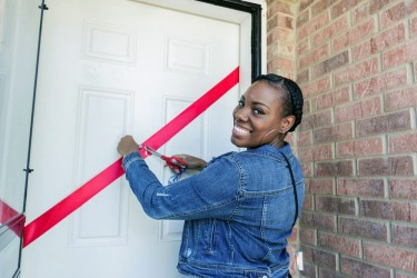 A Habitat homebuyer cuts the ribbon on the door of her new, affordable home