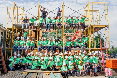 The 2017 Women Build volunteers flank the scaffolding of the home they funded and are helping build