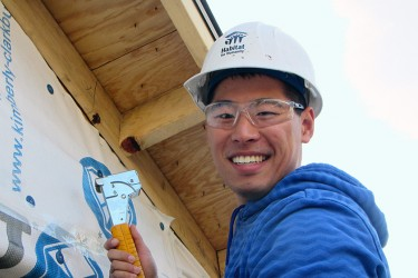 Volunteer on build site learns new construction skills