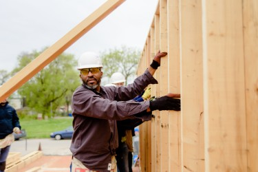 A proud volunteer raises a wall of a Habitat Chicago home