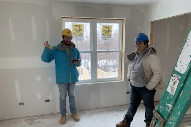 Two volunteers smile and wave on the Habitat Chicago build site