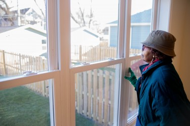 Woman smiles peacefully out on the backyard of a Habitat Chicago home