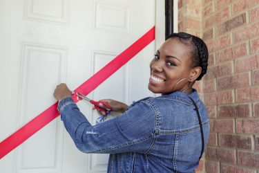 A new homeowner on the South Side of Chicago cuts the ribbon on her door