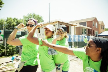 Women Builders flex after a hard day's work on the Habitat Chicago construction site