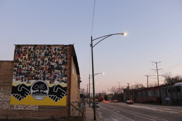 Community banner hanging on the side of a building in Greater Grand Crossing