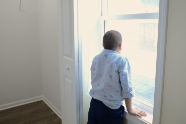 Boy looking out window in new Habitat home
