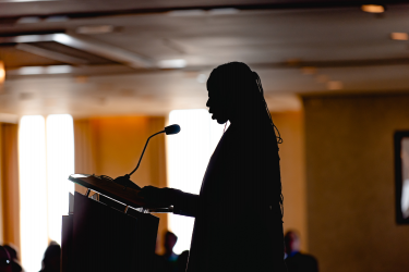 Silhouette speaking at a podium